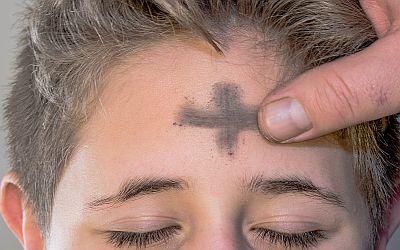 Finger zeichnet Aschenkreuz auf Stirn von Jungen