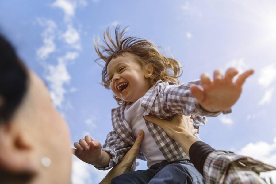 Kind fliegt freudig lachend in der Luft, von Elternteil in die Luft geworfen