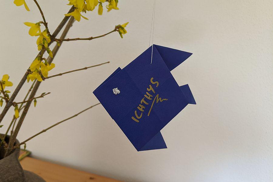 Origami-Fisch aus blauem Papier an Forsythienzweig