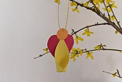 Engel aus Papier in Rot, Gelb und Orange an Forsythienzweigen