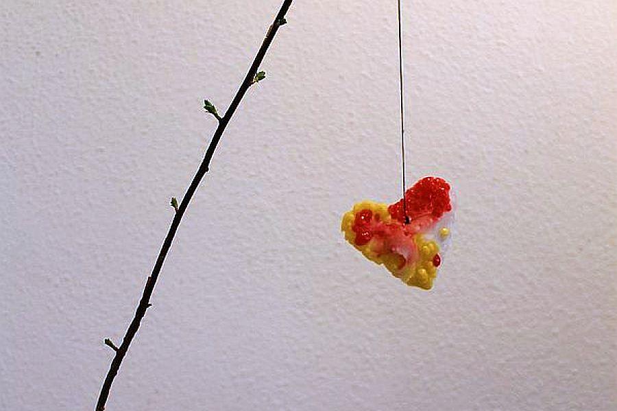 Herz aus Wachstropfen an Zweig