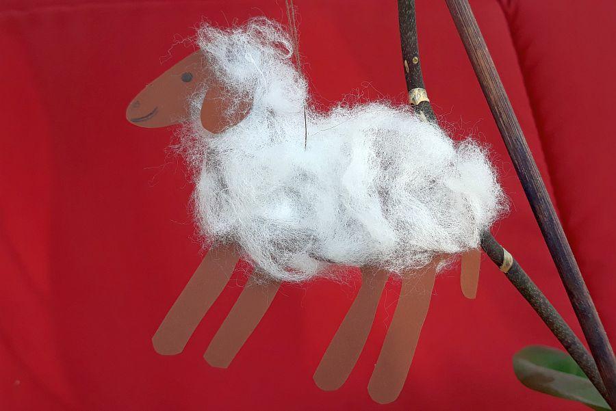 Schaf aus Papier und Watte an Zweig vor rotem Hintergrund