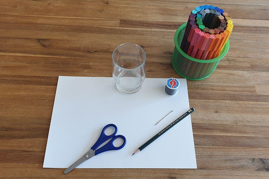 Glas, Filzstifte, Schere, Bindfaden, Nadel auf weißem Papier