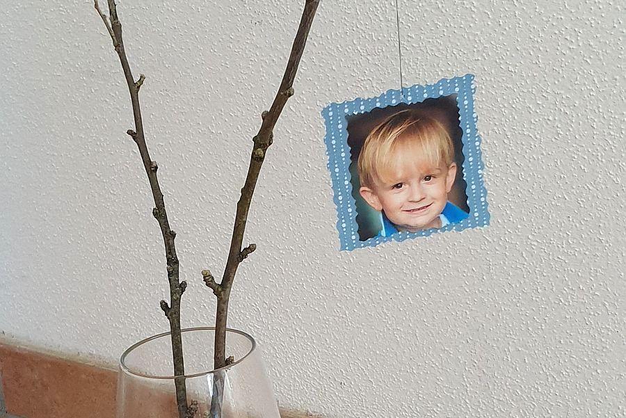 Passfoto mit verziertem Rahmen aus Papier hängt an Zweigen