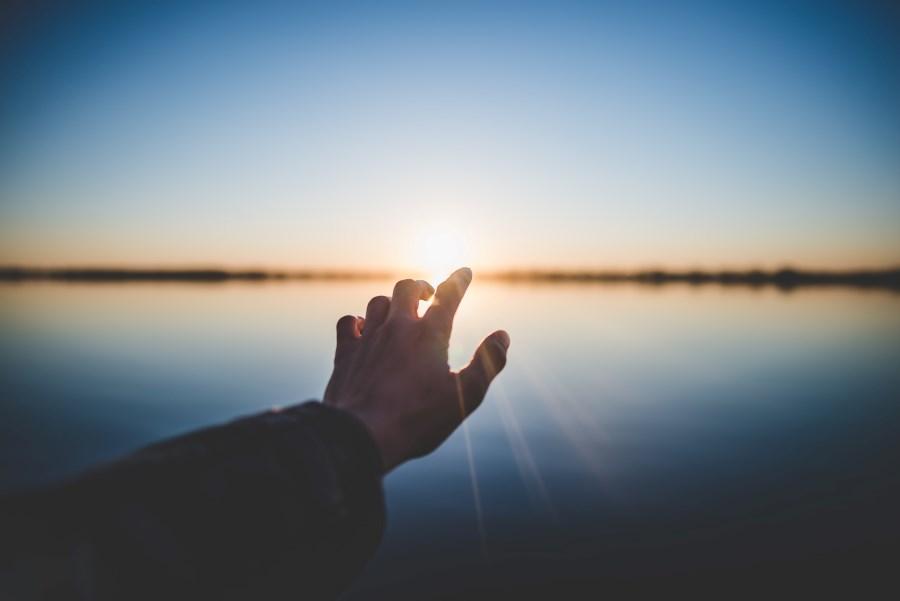 Hand streckt sich sehnsuchtsvoll in Richtung Sonnenuntergang