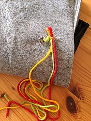 Gelber, grüner, roter Faden, mit Sicherheitsnadel an einem Stück Stoff befestigt
