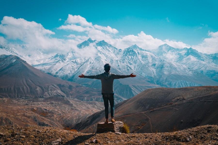 Mann streckt vor Bergtal weit die Arme aus