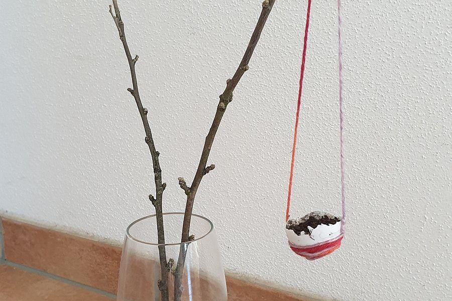 mit Wollfäden umwickelte und mit Erde gefüllte halbe Eierschale hängt an Zweig