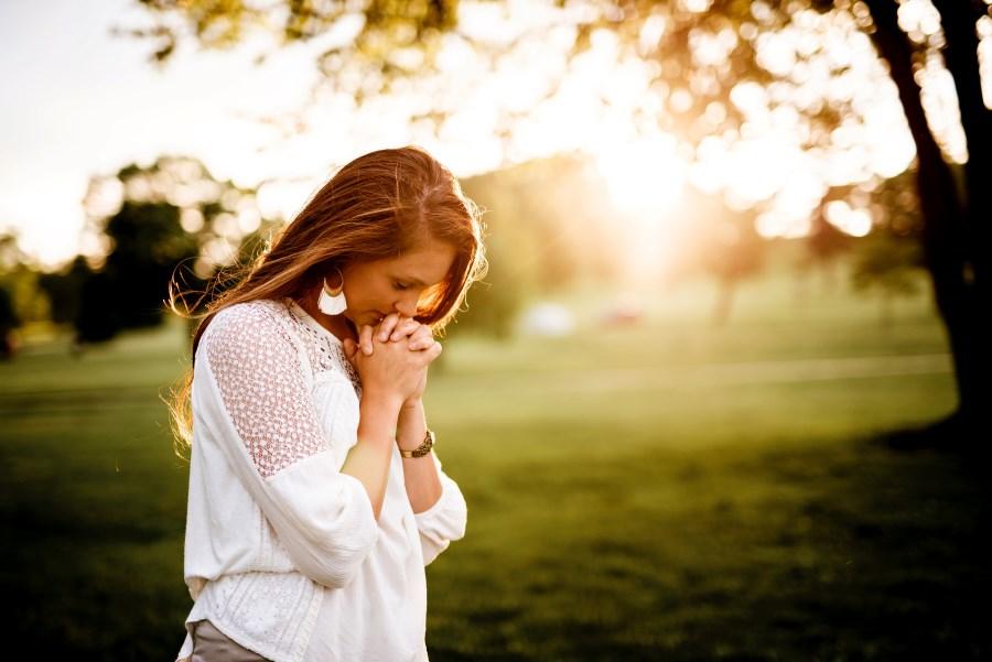junge Frau betet in der Natur