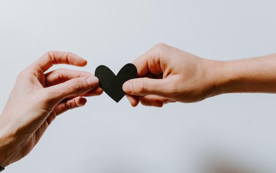 Hände halten ein Herz aus Papier