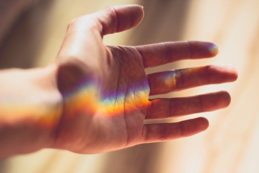 Hand, in der sich Regenbogen bildet