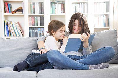 Zwei Mädchen sitzen mit Buch auf Couch