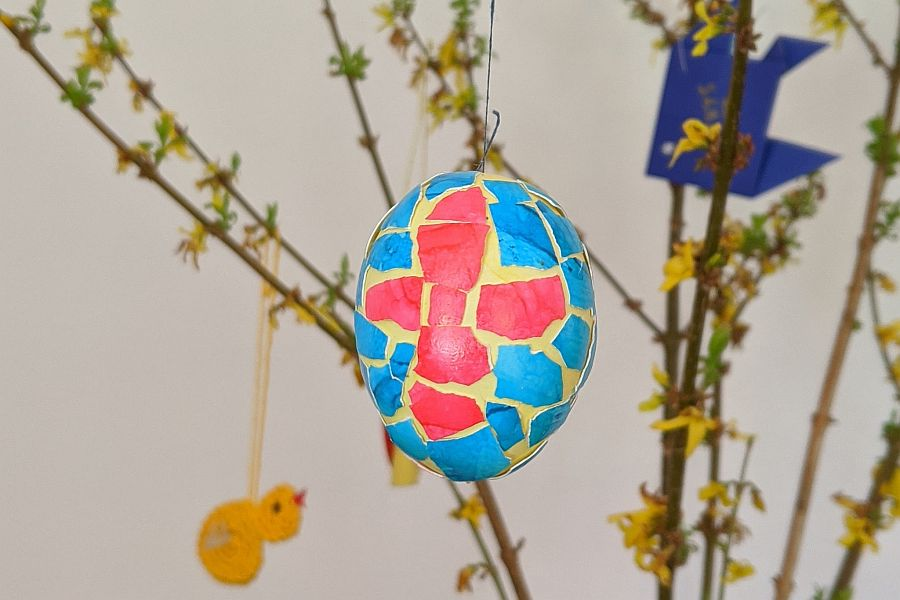 Ei, das mit mit bunten Scherben aus Eierschalen beklebt ist, an Zweigen