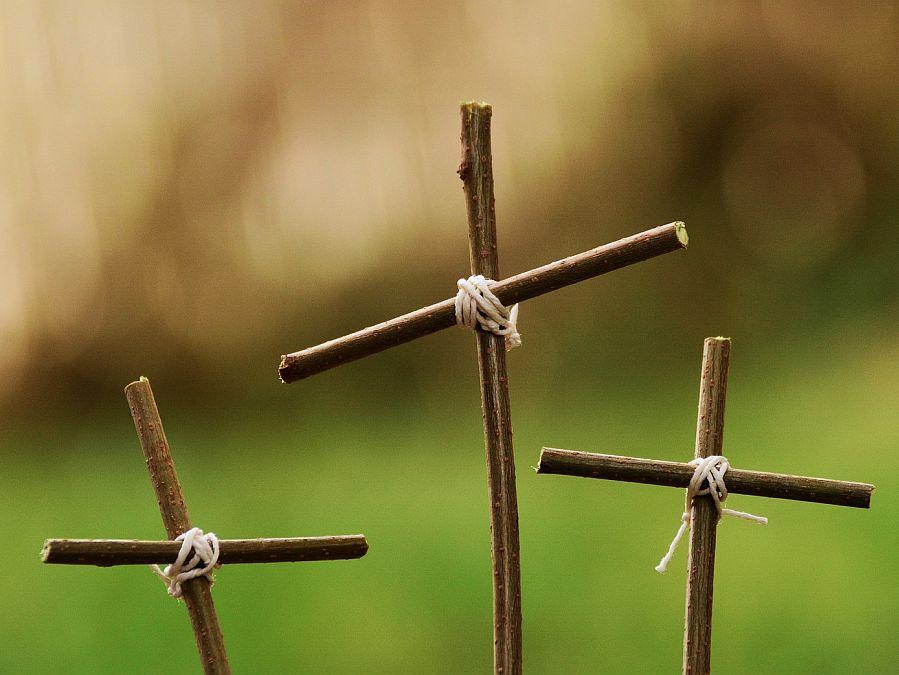 Drei Kreuze aus Ästen vor grüner Natur