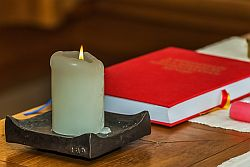 Brennende Kerze mit rotem Buch