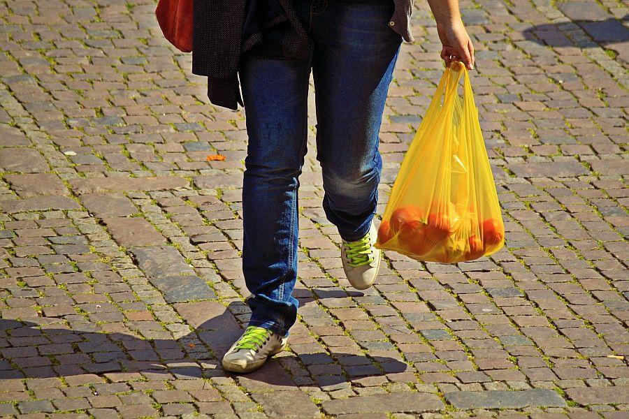 Beine und Hände von Frau mit Einkaufstüte