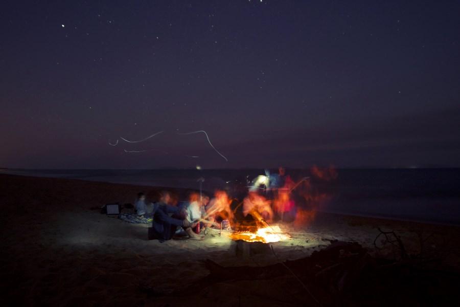 Gruppe Menschen sitzt um ein Lagerfeuer an einem Ufer am Abend