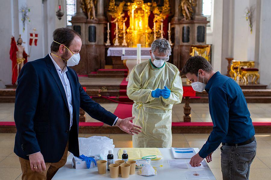 Drei Männer mit Schutzausrüstung um Altar mit Masken, Handschuhen, Bechern und Papieren