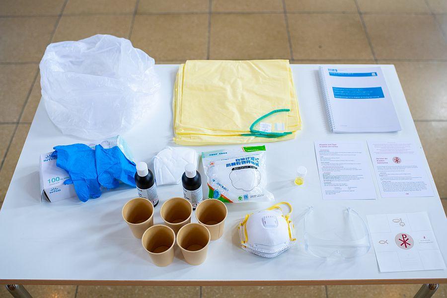Becher, Flaschen, Schutzanzüge, Masken, Papiere liegen auf einem Tisch