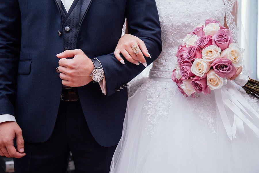 Hände von Hochzeitspaar in Hochzeitskleidung mit Brautstrauß