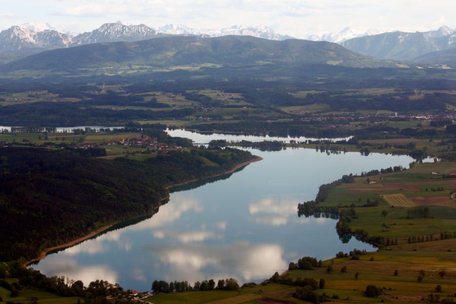 Blick auf Tachinger See mit Bergen im Hintergrund