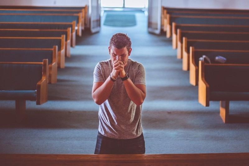Ein Mann bettet sehr intensiv alleine knieend vor dem Altar