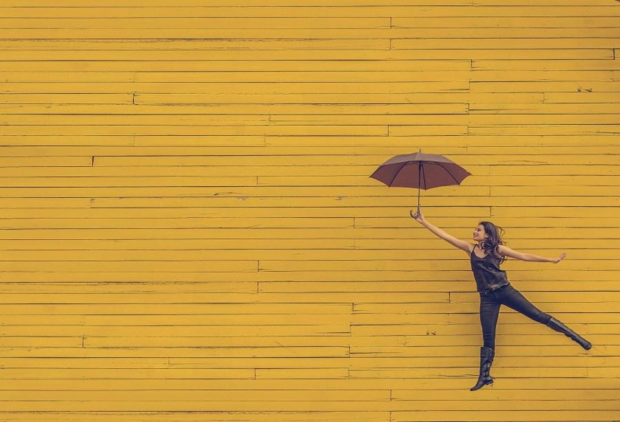 Frau fliegt mit Regenschirm vor gelber Wand