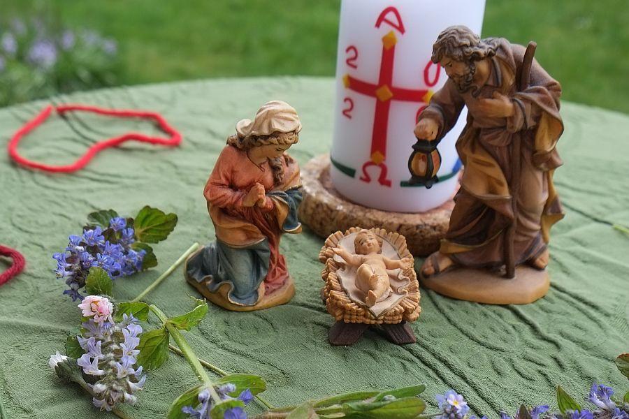 Maria mit Joseph und Kind in Krippe vor Osterkerze, rundherum Blumen