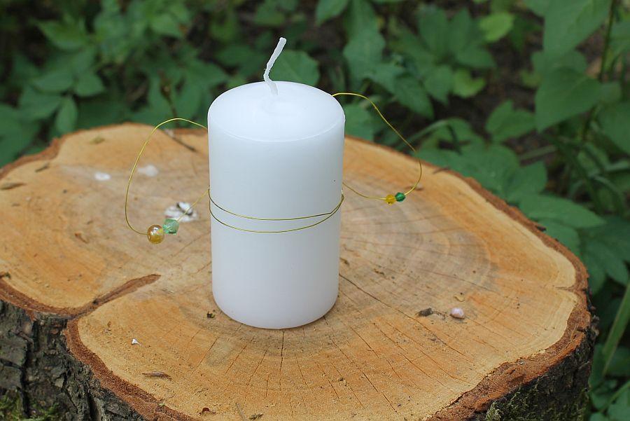 weiße Kerze mit Draht und Perlen auf Baumstumpf im Grünen