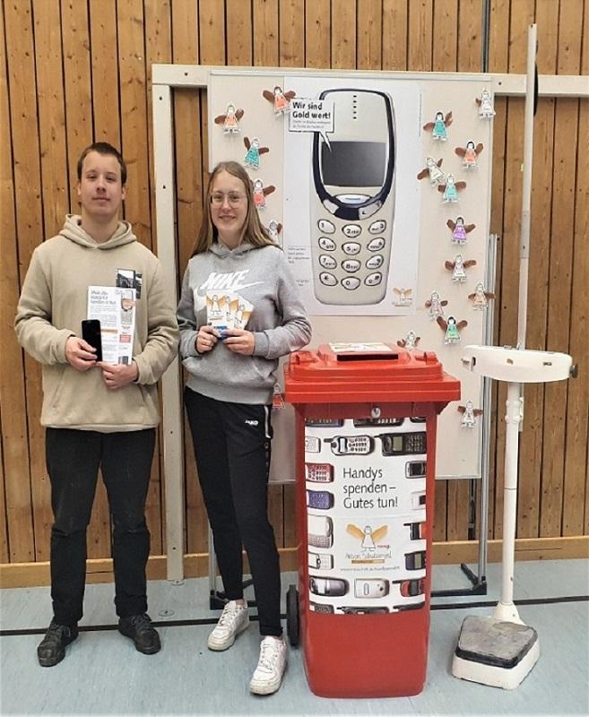 Stellvertretend nehmen die Schülersprecher 11,2 kg Transfair Schokolade für die gesammelten Handys entgegen.