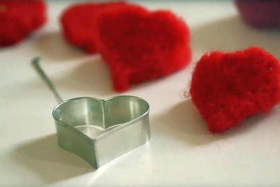 Herzen aus rotem Filz neben Plätzchenform Herz