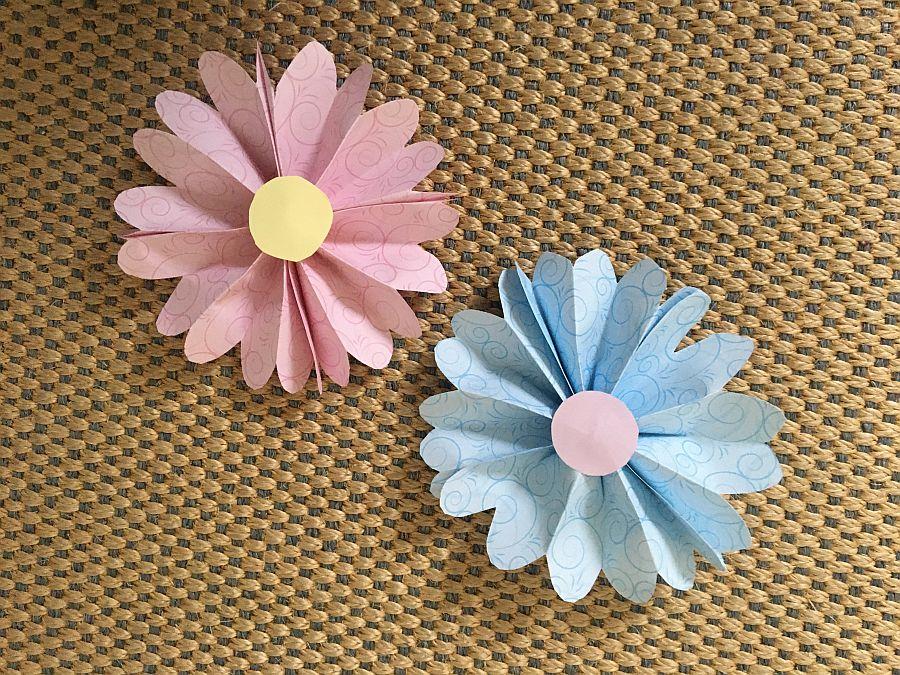 eine rosafarbene und eine hellblaue Papierblume auf grobem Stoff