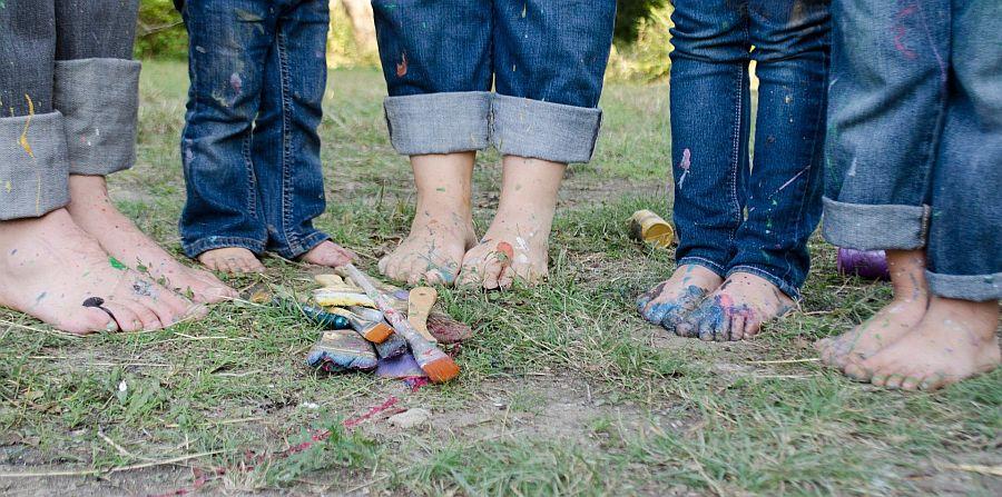 fünf Paar nackte, mit Farben beschmierte Füße in Jeans