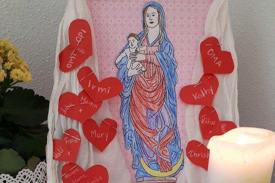 bunt ausgemaltes Marienbild, darum ein weißes Tuch geschmückt mit roten Herzen