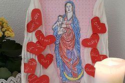 ausgemaltes Marienbild mit weißem Tuch und roten Herzen