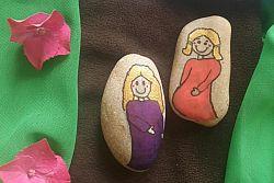 zwei mit Frauenfiguren bemalte Steine auf braunem und grünem Tuch