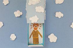 Streichholzschachtel mit Bild von Jesus auf blauem Papier mit weißen Wattewolken