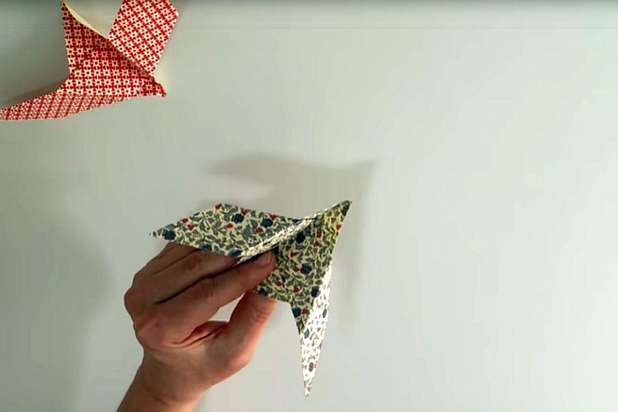 Hand hält Origami-Taube aus gemustertetem Papier, daneben zweite Taube