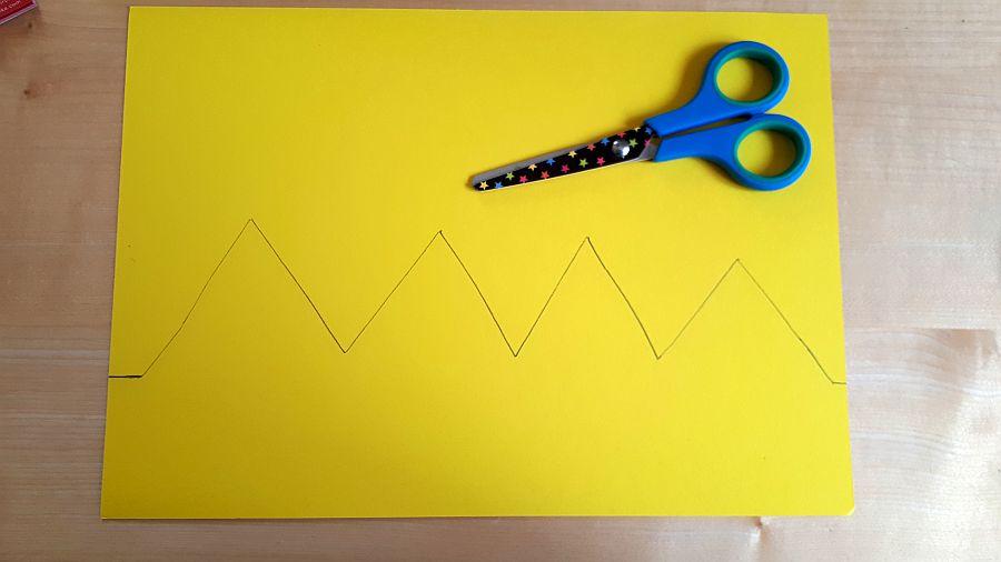 gelbes Tonpapier mit aufgemalten Zacken und Schere