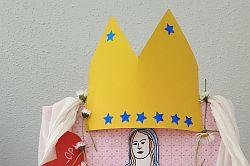 gelbe Krone mit blauen Sternen als Krönung von mit Mantel geschmückter Marienstatue