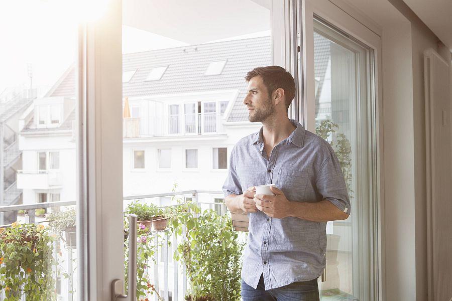 Mann mit Tasse in der Hand blickt nachdenklich aus dem Fenster