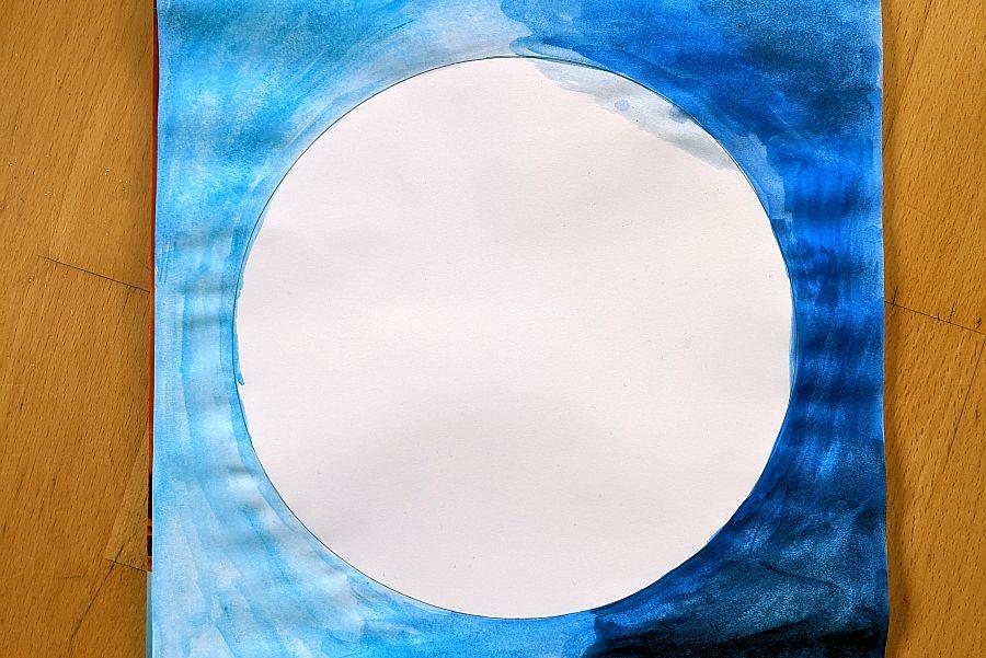 Blatt mit weißem Kreis in der Mitte, daneben eine Hälfte mit hellblauer und andere Hälfte mit dunkelblauer Wasserfaben ausgemalt