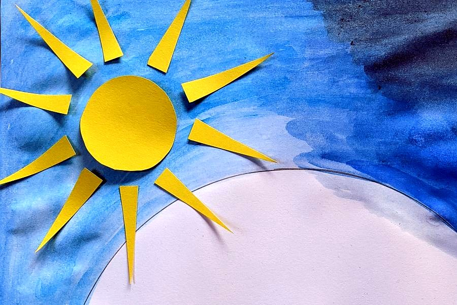 gelbe Sonne aus Tonpapier auf mit blauer Wasserfarbe bemaltem Papier