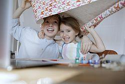zwei Kinder halten lachend Bogen Geschenkpapier über sich