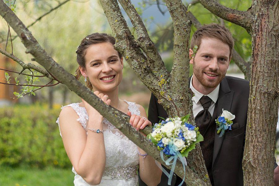 Braut und Bräutigam schauen glücklich hinter Zweigen eines Baums hervor