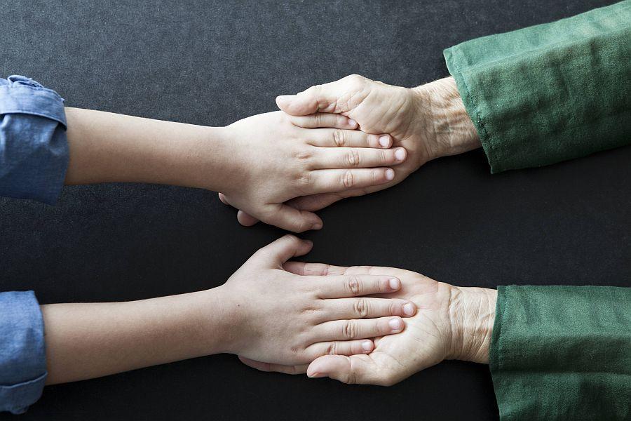 ein Paar Kinderhände und ein Paar Seniorenhände liegen ineinander