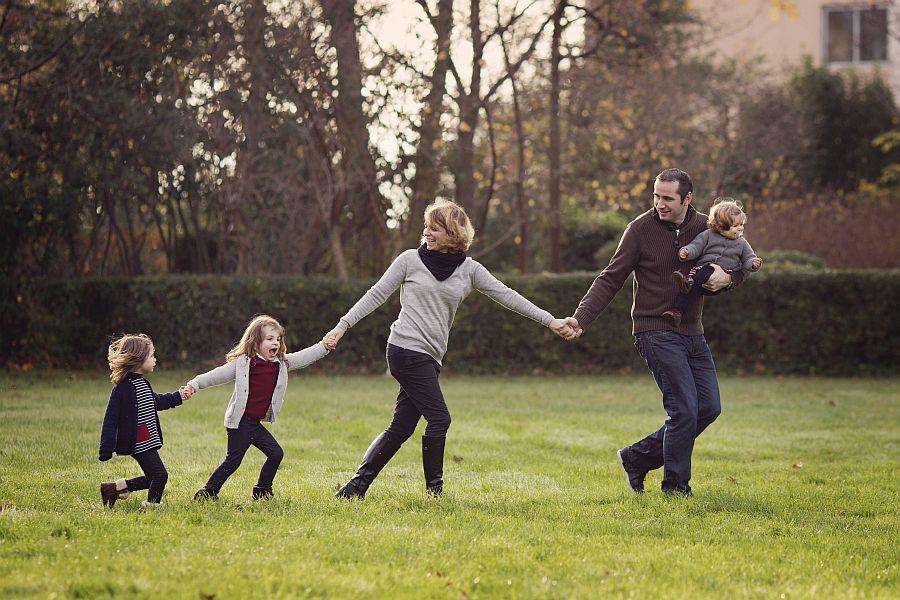 Eltern und drei Kinder laufen in Reihe über Wiese und halten sich an der Hand