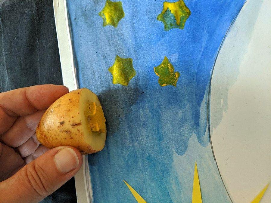 Hand stempelt mit Kartoffel gelben Stern auf blau bemaltes Papier