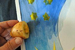Hand stempelt gelbe Sterne mit Kartoffel-Stempel auf blau bemaltes Papier