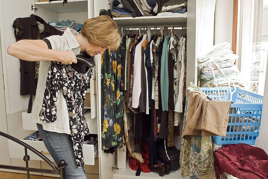 Frau vor Kleiderschrank hält sich testend Bluse vor den Körper